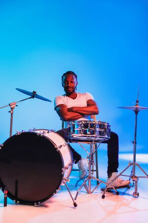 Young african-american jazz musician or drummer playing drums on blue studio background in trendy neon lights. Concept of music, hobby, inspirness. Colorful portrait of joyful attractive artist. 版權商用圖片