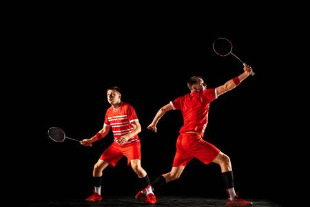 Young man playing badminton isolated on black background in mixed light. Male model in sportwear and sneakers with the racket in action, motion in game. Concept of sport, movement, healthy lifestyle.