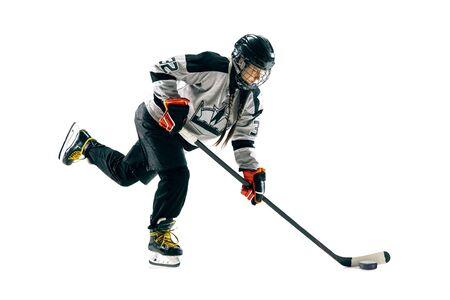 Junge Hockeyspielerin mit dem Stock auf weißem Hintergrund. Sportlerin in Aktion mit Ausrüstung, die für das Tor oder die Punktzahl angreift. Konzept des Sports, des gesunden Lebensstils, der Bewegung, der Bewegung.
