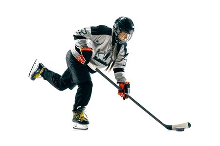 Young female hockey player with the stick isolated on white background. Sportswoman in action wearing equipment attacking for the goal or score. Concept of sport, healthy lifestyle, motion, movement.