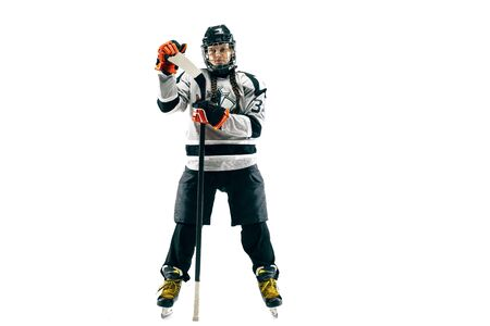 Young female hockey player isolated on white background. Sportswoman wearing equipment and helmet standing with the stick. Concept of sport, healthy lifestyle, motion, movement, action.