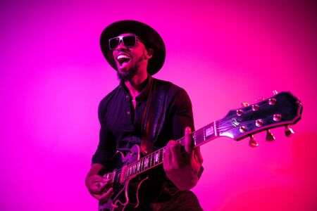 Young african-american musician playing the guitar like a rockstar on gradient purple-pink background in neon light. Concept of music, hobby. Joyful attractive guy improvising and singing a song. 写真素材