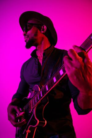 Young african-american musician playing the guitar like a rockstar on gradient purple-pink background in neon light. Concept of music, hobby. Joyful attractive guy improvising. Colorful portrait.