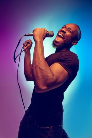 Young african-american jazz musician singing a song on gradient purple-blue background. Concept of music, hobby. Joyful attractive guy improvising, having a concert. Colorful retro portrait of singer. Фото со стока