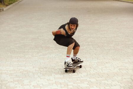 Skateboarder doing a trick at the city street in cloudy day. Young man in sneakers and cap riding and long boarding on the asphalt. Concept of leisure activity, sport, extreme, hobby and motion. Banco de Imagens