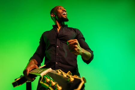 Young african-american musician playing the guitar like a rockstar on gradient green-yellow background. Concept of music, hobby, festival, open-air. Joyful attractive guy improvising, singing song.