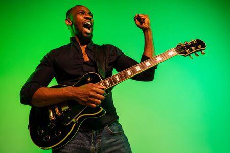 Jeune musicien afro-américain jouant de la guitare comme une rockstar sur fond dégradé vert-jaune. Concept de musique, passe-temps, festival, plein air. Un mec séduisant et joyeux improvise, chante une chanson.
