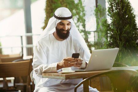 Arabischer saudischer Geschäftsmann, der online mit einem Laptop und einem Tablet in einem Café oder einem Café mit einer Außenterrasse im Hintergrund arbeitet. Geschäftskonzept, Finanzen, moderne Technologien, Start.