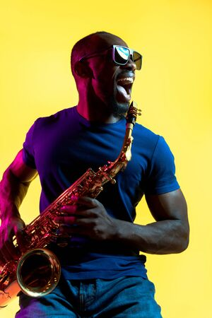 Young african-american jazz musician playing the saxophone on yellow studio background in trendy neon light. Concept of music, hobby. Joyful attractive guy improvising. Colorful portrait of artist.