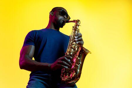 Jeune musicien de jazz afro-américain jouant du saxophone sur fond de studio jaune dans un néon à la mode. Concept de musique, passe-temps. Joyeux mec attirant improvisant. Portrait coloré de l'artiste.