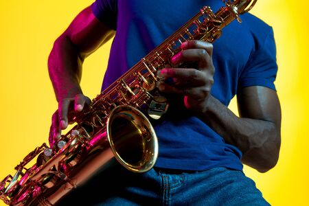 Young african-american jazz musician playing the saxophone on yellow studio background in trendy neon light. Concept of music, hobby. Joyful attractive guy improvising. Colorful portrait of artist. Banque d'images
