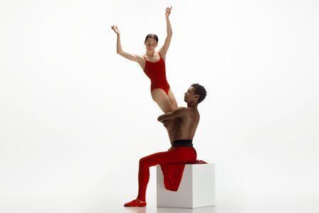 Graziosi ballerini di balletto classico che ballano isolati su sfondo bianco per studio. Coppia in abiti rosso vivo come una combinazione di vino e latte. Il concetto di grazia, artista, movimento, azione e movimento.