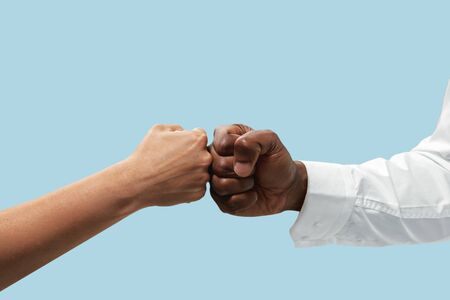 Friends greetings sign or disagreement. Two male hands competion in arm wrestling isolated on blue studio background. Concept of standoff, support, friendship, business, community, strained relations. Stock fotó