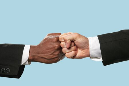 Friends greetings sign or disagreement. Two male hands competion in arm wrestling isolated on blue studio background. Concept of standoff, support, friendship, business, community, strained relations. Stock Photo