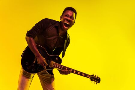 Young african-american musician playing the guitar like a rockstar on yellow background in neon light. Concept of music, hobby, festival, open-air. Joyful attractive guy improvising, singing song. 写真素材