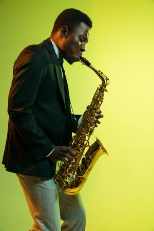 Young african-american jazz musician playing the saxophone on gradient yellow-green studio background. Concept of music, hobby, festival. Joyful attractive guy improvising. Colorful portrait of artist. Stock Photo