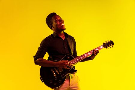 Young african-american musician playing the guitar like a rockstar on yellow background in neon light. Concept of music, hobby, festival, open-air. Joyful attractive guy improvising, singing song. Reklamní fotografie