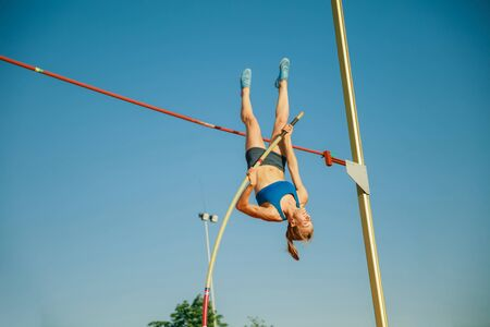 Professional female high jumper training at the stadium in sunny day. Fit female model practicing in high jumps outdoors. Concept of sport, activity, healthy lifestyle, action, movement, motion.