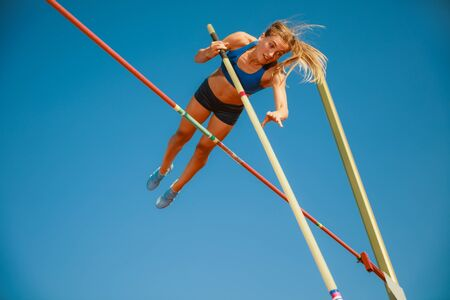 Professional female high jumper training at the stadium in sunny day. Fit female model practicing in high jumps outdoors. Concept of sport, activity, healthy lifestyle, action, movement, motion. 写真素材