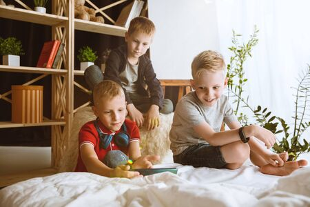Boys using different gadgets at home. Little models with smart watches, smartphone or tablet and headphones. Making selfie, chating, gaming, watching videos. Interaction of kids and modern technologies.