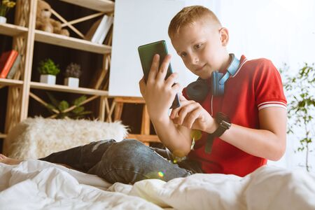 Boy using different gadgets at home. Little model with smart watches, smartphone or tablet and headphones. Making selfie, chating, gaming, watching videos. Interaction of kids and modern technologies.