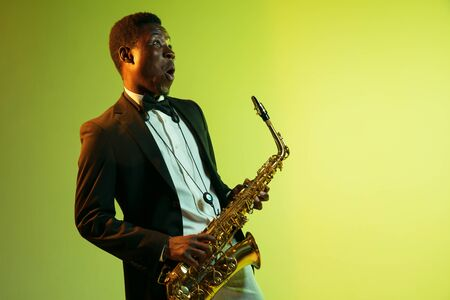 Young african-american jazz musician playing the saxophone on gradient yellow-green studio background. Concept of music, hobby, festival. Joyful attractive guy improvising. Colorful portrait of artist. Banque d'images