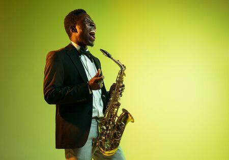 Jeune musicien de jazz afro-américain jouant du saxophone sur fond de studio dégradé jaune-vert. Concept de musique, passe-temps, festival. Joyeux mec attirant improvisant. Portrait coloré de l'artiste.
