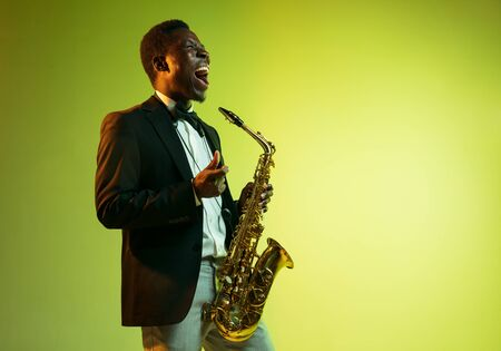 Young african-american jazz musician playing the saxophone on gradient yellow-green studio background. Concept of music, hobby, festival. Joyful attractive guy improvising. Colorful portrait of artist.