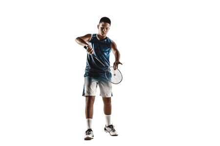 Little boy playing badminton isolated on white studio background. Young male model in sportwear and sneakers with the racket in action, motion in game. Concept of sport, movement, healthy lifestyle.