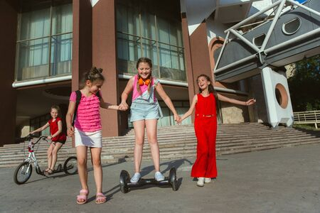 Happy kids playing at citys street in sunny summers day in front of modern building. Group of happy childrens or teenagers having fun together. Concept of friendship, childhood, summer, holidays.