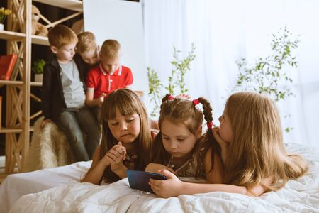 Boys and girls using different gadgets at home. Childs with smart watches, smartphone and headphones. Making selfie, chating, gaming, watching videos. Interaction of kids and modern technologies.
