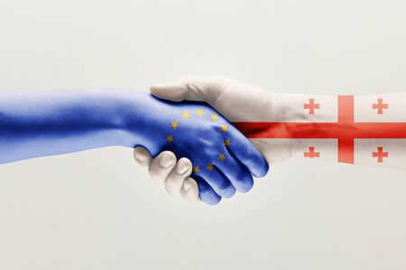 Supporting gesture. Two male hands shaking colored in flag of European Unity and Georgia isolated on white studio background. Concept of help, partnership of countries, political and economical relati 스톡 콘텐츠