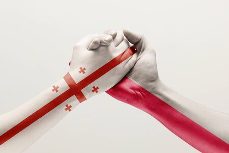 Supporting gesture. Two male hands shaking colored in flag of Poland and Georgia isolated on white studio background. Concept of help, partnership of countries, political and economical relations.