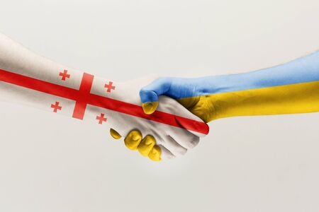 Supporting gesture. Two male hands shaking colored in flag of European Unity and Ukraine isolated on white studio background. Concept of help, partnership of countries, political and economical relati 스톡 콘텐츠