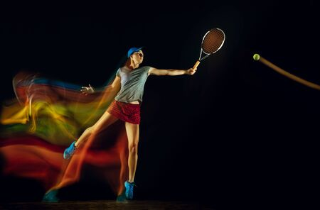 One caucasian woman playing tennis isolated on black background in mixed and stobe light. Fit young female player in motion or action during sport game. Concept of movement, sport, healthy lifestyle.