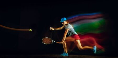 One caucasian woman playing tennis isolated on black background in mixed and stobe light. Fit young female player in motion or action during sport game. Concept of movement, sport, healthy lifestyle. Stock Photo - 126259421