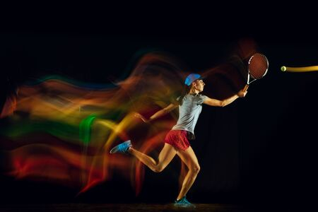 One caucasian woman playing tennis isolated on black background in mixed and stobe light. Fit young female player in motion or action during sport game. Concept of movement, sport, healthy lifestyle. Stock Photo - 126259423