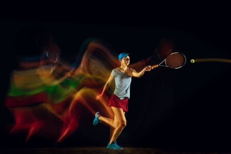 One caucasian woman playing tennis isolated on black background in mixed and stobe light. Fit young female player in motion or action during sport game. Concept of movement, sport, healthy lifestyle. Stock Photo - 126259424