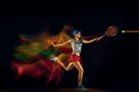 One caucasian woman playing tennis isolated on black background in mixed and stobe light. Fit young female player in motion or action during sport game. Concept of movement, sport, healthy lifestyle. Stock Photo - 126259426