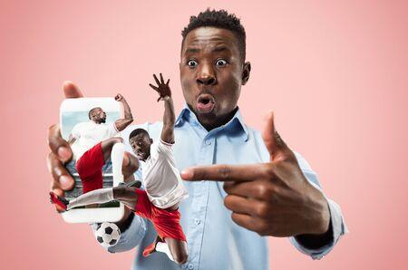 Porträt des Mannes, der Bildschirm des Handys lokalisiert über korallenrotem Hintergrund zeigt. Männliches Model mit Smartphone für Wetten und Sportübersetzungen. Kreative Collage aus 2 Personen.