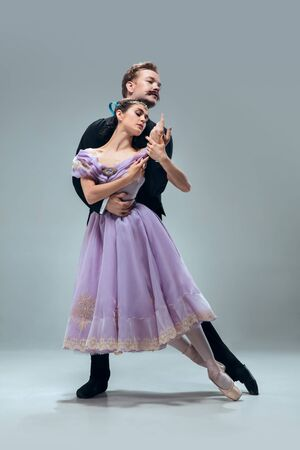 Absolute trust. Beautiful contemporary ballroom dancers isolated on grey studio background. Sensual proffessional artists dancing walz, tango, slowfox and quickstep. Flexible and weightless.