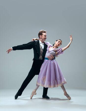 Meereswellen. Schöne zeitgenössische Ballsaaltänzer lokalisiert auf grauem Studiohintergrund. Sinnliche Profi-Künstler tanzen Walzer, Tango, Slowfox und Quickstep. Flexibel und schwerelos.