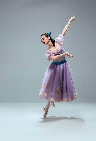 Schwerelosigkeit. Schöne zeitgenössische Ballsaaltänzerin auf grauem Studiohintergrund isoliert. Sinnliche professionelle Künstlerin tanzt Walzer, Tango, Slowfox und Quickstep. Flexibel und schwerelos. Standard-Bild