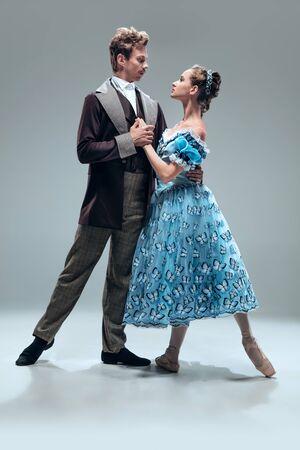 Romantische Atmosphäre. Schöne zeitgenössische Ballsaaltänzer lokalisiert auf grauem Studiohintergrund. Sinnliche Profi-Künstler tanzen Walzer, Tango, Slowfox und Quickstep. Flexibel und schwerelos.