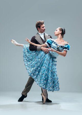 Gerader Blick. Schöne zeitgenössische Ballsaaltänzer lokalisiert auf grauem Studiohintergrund. Sinnliche Profi-Künstler tanzen Walzer, Tango, Slowfox und Quickstep. Flexibel und schwerelos.