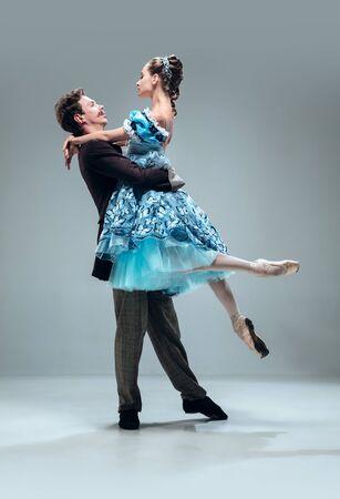 Über der Welt. Schöne zeitgenössische Ballsaaltänzer lokalisiert auf grauem Studiohintergrund. Sinnliche Profi-Künstler tanzen Walzer, Tango, Slowfox und Quickstep. Flexibel und schwerelos.