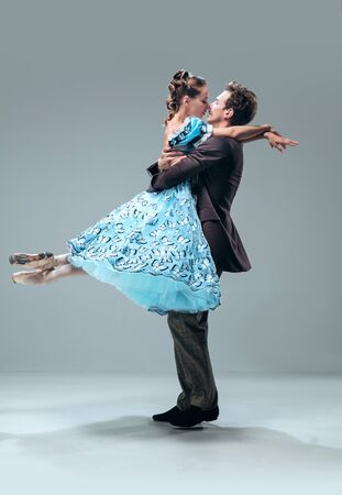 Zärtlichkeit. Schöne zeitgenössische Ballsaaltänzer lokalisiert auf grauem Studiohintergrund. Sinnliche Profi-Künstler tanzen Walzer, Tango, Slowfox und Quickstep. Flexibel und schwerelos.