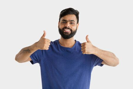 Beautiful male half-length portrait isolated on white studio background. Young emotional hindu man. Facial expression, human emotions, advertising concept. Happy, showing the sign of nice or cool.