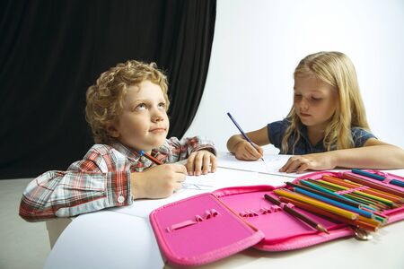 Boy and girl preparing for school after a long summer break. Back to school. Little caucasian models drawing together on white and black background. Childhood, education, holidays or homework concept.