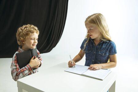 Boy and girl preparing for school after a long summer break. Back to school. Little caucasian models making homework together on studio background. Childhood, education, holidays or homework concept.